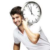 Portrait of a handsome young man carrying a clock against a whit — Stock Photo