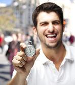 Ritratto di giovane uomo ridendo e mostrando un cronometro a un corvo — Foto Stock