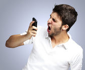 Portrait of angry young man shouting using mobile over blue back — Stock Photo
