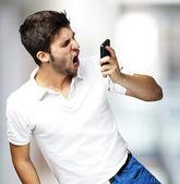 Kızgın genç adam cep kapalı kullanarak bağırarak portresi — Stok fotoğraf