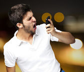 Portrait of angry young man shouting using mobile against a abst — Stock Photo