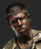 Young soldier with camouflage paint looking very serious over bl — Stock Photo