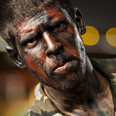 Young soldier with camouflage paint looking very serious at city — Stock Photo