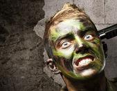 Portrait du suicide de comiting du jeune soldat contre un mur de grunge — Photo