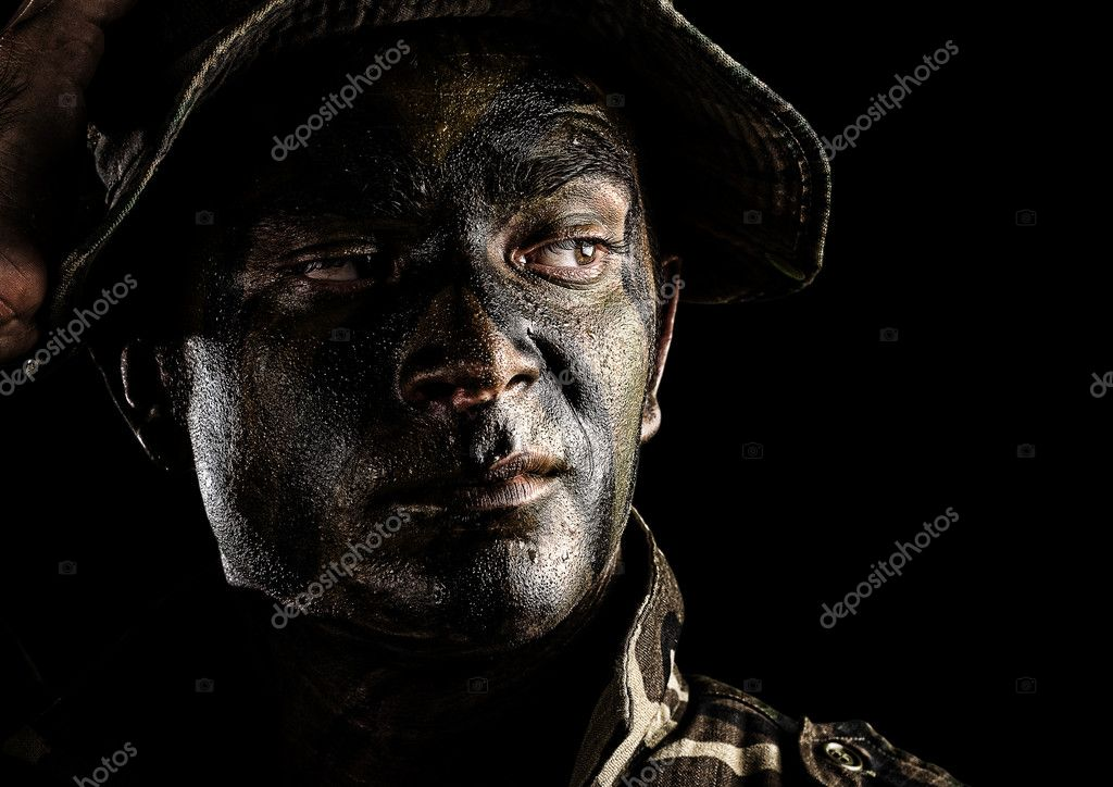 Portrait of young soldier face with jungle camouflage over black background — Stock Photo #10173076
