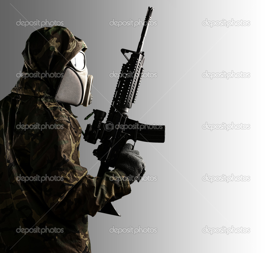 Portrait of soldier with mask and rifle against a grey background — Stock Photo #10173302