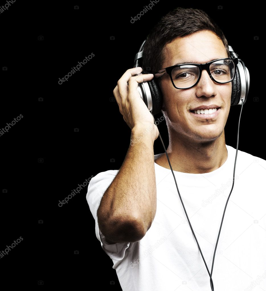 Portrait of young man smiling and listening to music against a black background — Stock Photo #10175711