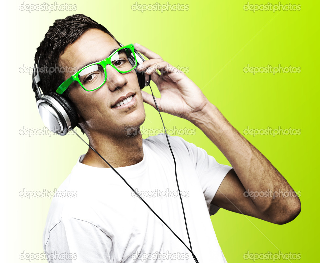 Portrait of young man with green glasses listening to music on a green background — Stock Photo #10175723