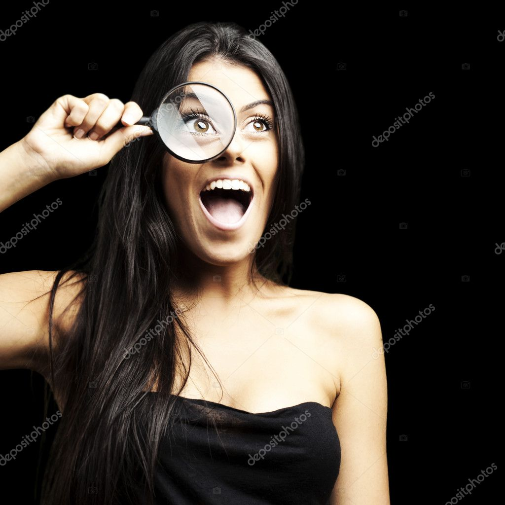 Portrait of woman excited looking through a magnifying glass over black background — Stock Photo #10176008