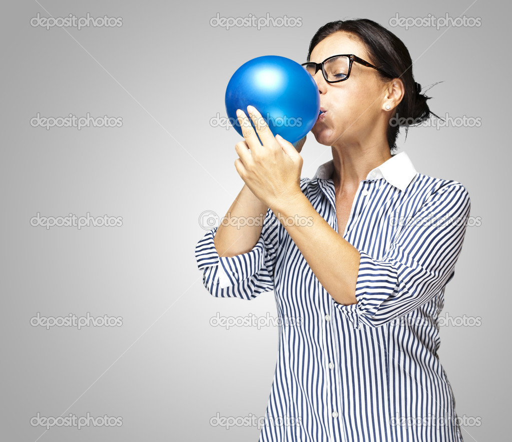 Portrait of a middle aged woman blowing a balloon against a grey background — Stock Photo #10177114