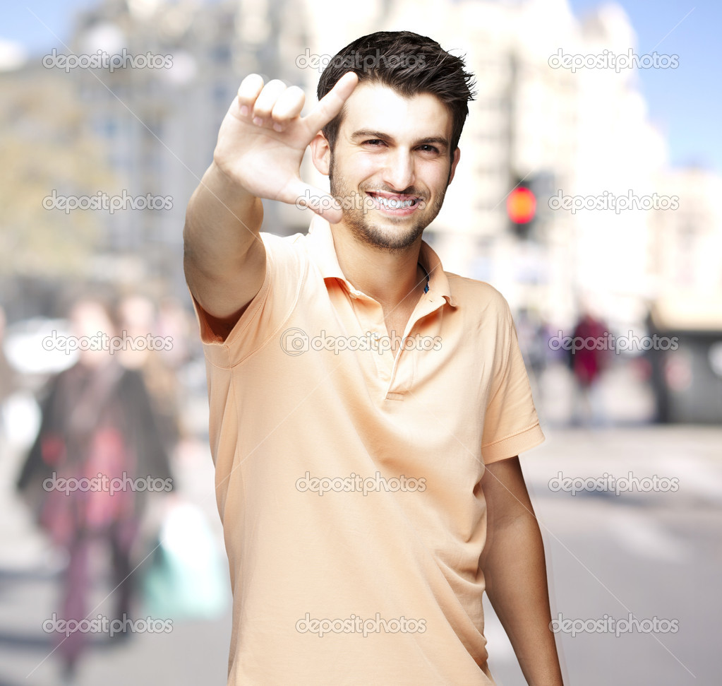 Portrait of a handsome man doing good symbol at a crowded city  Stock Photo #10177587