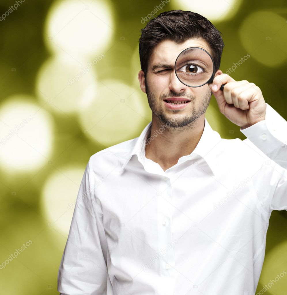 Portrait of young man looking through a magnifying glass against a abstract background — Stock Photo #10178008