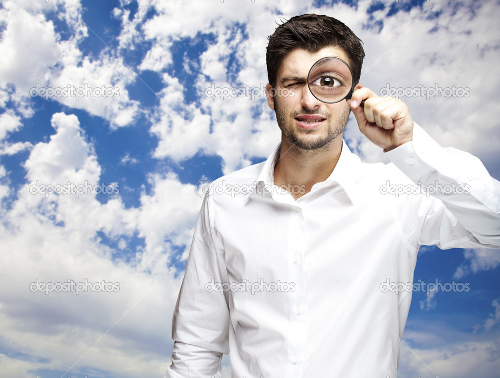 Portrait of young man looking through a magnifying glass against a cloudy sky background — Stock Photo #10178016