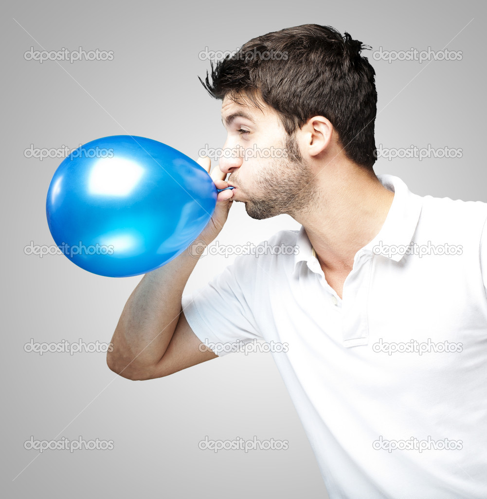 Portrait of young man blowing a balloon over grey background  Stock Photo #10178408