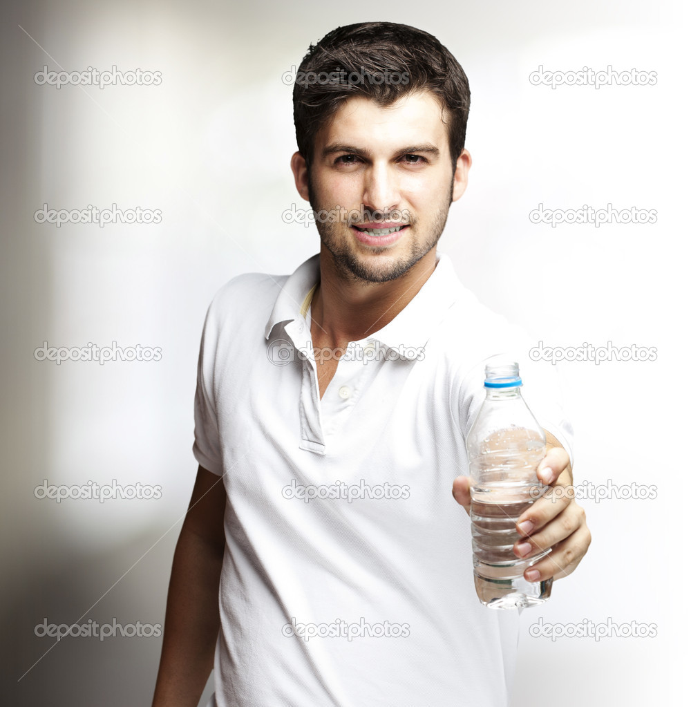 Portrait of a young man offering a water bottle — Stock Photo #10178447