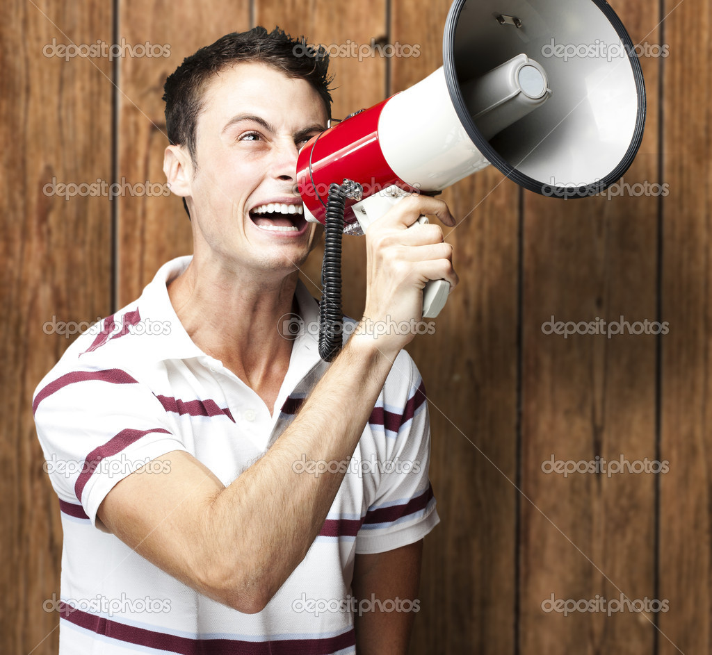 Portrait of young man shouting with megaphone against a wooden wall — Stock Photo #10178533