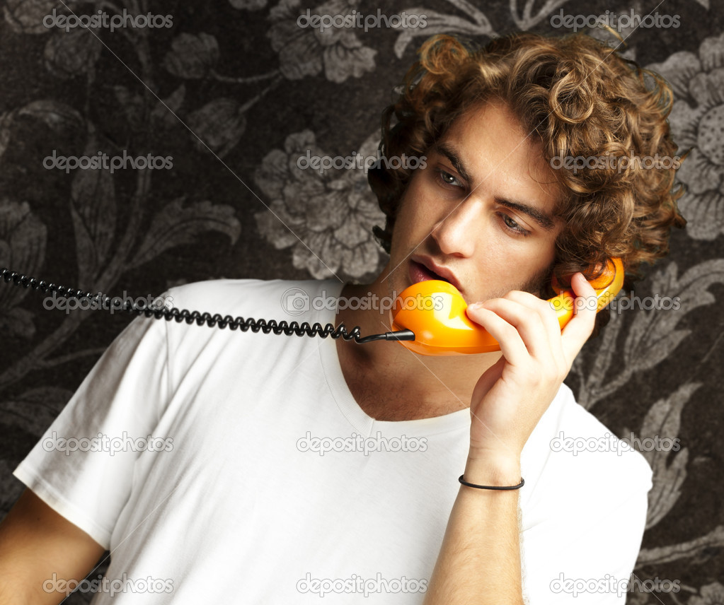 Portrait of young man talking on a vintage telephone against a vintage wall — Stock Photo #10179184