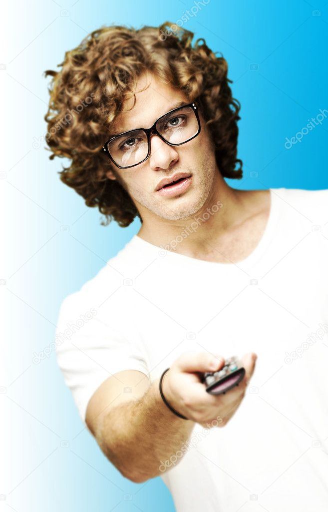 Portrait of young man with glasses changing channel with tv control over blue — Stock Photo #10179274