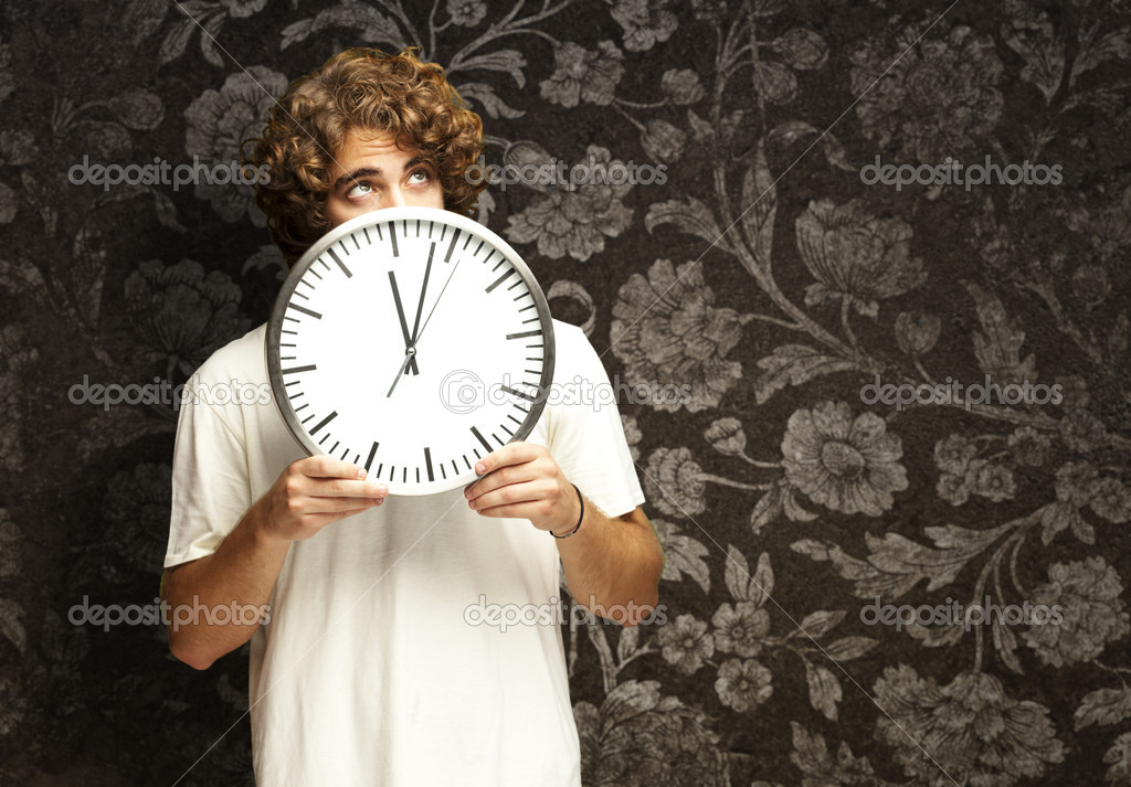 Scared young man hidden behind a clock against a vintage wall — Stock Photo #10179311