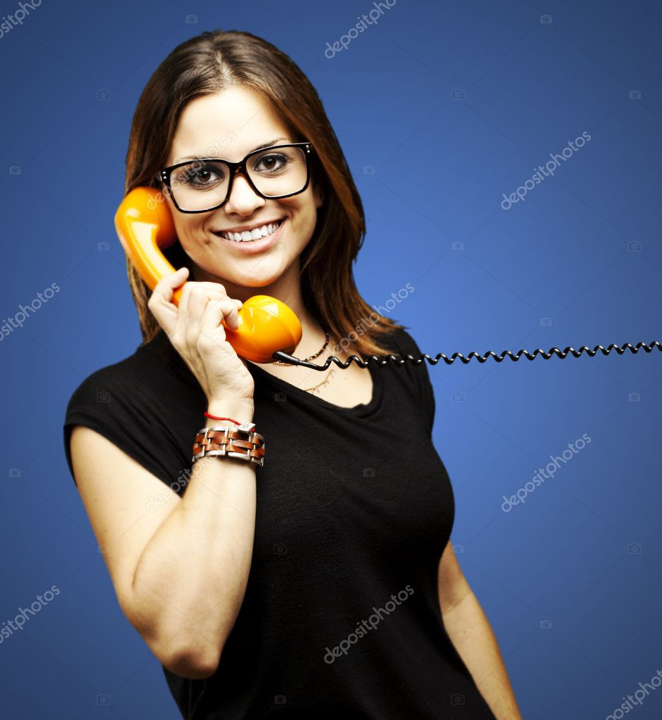 Portrait of young woman talking using vintage telephone over blue background — Stock Photo #10179703