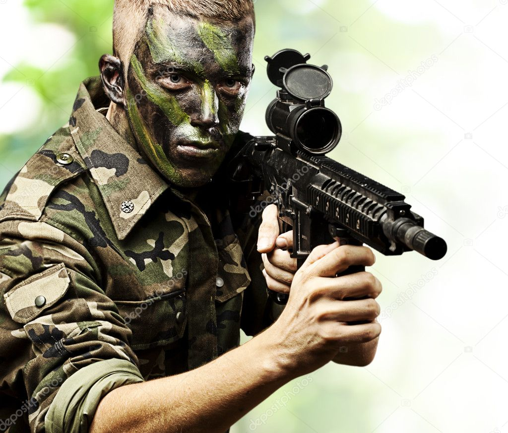 Portrait of young soldier pointing with rifle in the jungle — Stock Photo #10179933