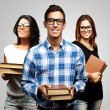 Young students holding books over grey background — Stock Photo