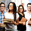 Portrait of young students holding books at street — Stock Photo #10180100