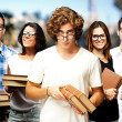 Royalty-Free Stock Photo: Portrait of young students holding books at street