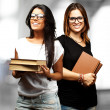 Portrait of young students holding books indoor - Foto Stock