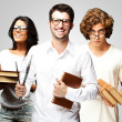 Portrait of young students holding books over grey background — Stock Photo
