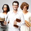 Stock Photo: Portrait of young students holding books over grey background