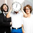 Young man holding clock with friends at city — Stock Photo