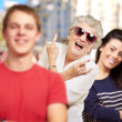 Young friends with grandmother having fun at street — Stock Photo