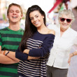 Young friends with grandmother smiling at street — Stock Photo