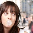 Portrait of young woman listening to music with bubble gum at cr — Stock Photo #10180310