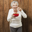 Senior woman eating cereals out of a red bowl against a wooden b — Stock Photo