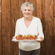 Portrait of senior woman showing homemade muffins against a wood — Stock Photo #10180382