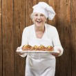 Senior woman cook holding a tray with muffins against a wooden b — Stock Photo #10180390