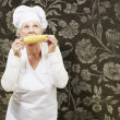 Senior woman cook eating a corncob against a vintage background — Stock Photo