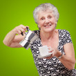 Portrait of a vitality senior woman serving a tea cup over green — Stock Photo #10180459