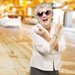 Royalty-Free Stock Photo: Portrait of senior woman doing rock symbol against a city night