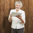 Portrait of senior woman touching digital tablet against a woode - Stock Photo
