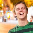 Portrait of young man smiling against a night city - Lizenzfreies Foto