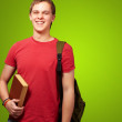 Portrait of young student holding book and carrying backpack ove — Stock Photo