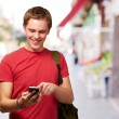 Portrait of young man touching mobile screen at street — Stock Photo