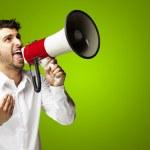 Porträt des jungen Mannes schreien mit Megafon über grüne backgro — Stockfoto