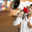 Portrait of young man shouting with megaphone at city by night — Stock Photo