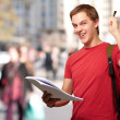 Portrait of handsome student holding notebook and pen at crowded — Stock Photo