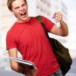 Young angry student man roughing a sheet against a university — Stock Photo