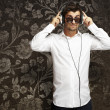 Portrait of young man listening to music using headphones agains — Stock Photo #10180587